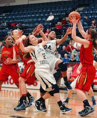 Liberty Christian freshman guard Rebekah Hand (12) and senior forward RayVon Christian (24) go after a rebound against Plano John Paul II in the TAPPS Class 5A state championship game Saturday at Mansfield Legacy. John Paul II won 46-39.David Minton - DRC